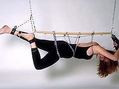 Torture Pictures -  Blonde in leotard is chained to ceiling and stripped