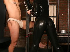 BDSM Pictures -  Mistress Anastasia silences her moaning malesub by gagging his mouth with a duct tape