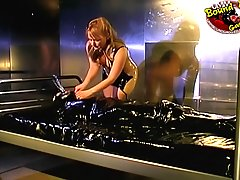 Pain Pictures -  Amateur brunette in bondage gets whipped by the mistress in rubber dress