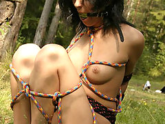Outdoors Pictures -  Gagged female slave suffers rope bondage pain outdoors