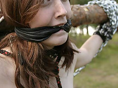 Punishment Pictures -  Young slave is roped and chained outdoors with clips on her nipples