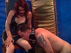 Transgender Pictures -  Tranny mistress ties her servant's cock and has him lick her leather top-boots