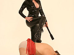 BDSM Pictures -  Hot amateur mistress in black latex overall poses before femdom session
