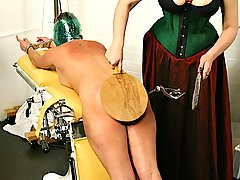 Fetish Pictures -  FetishNetwork.com - Ms Bridgett gives Graziella a thorough exam with the paddle